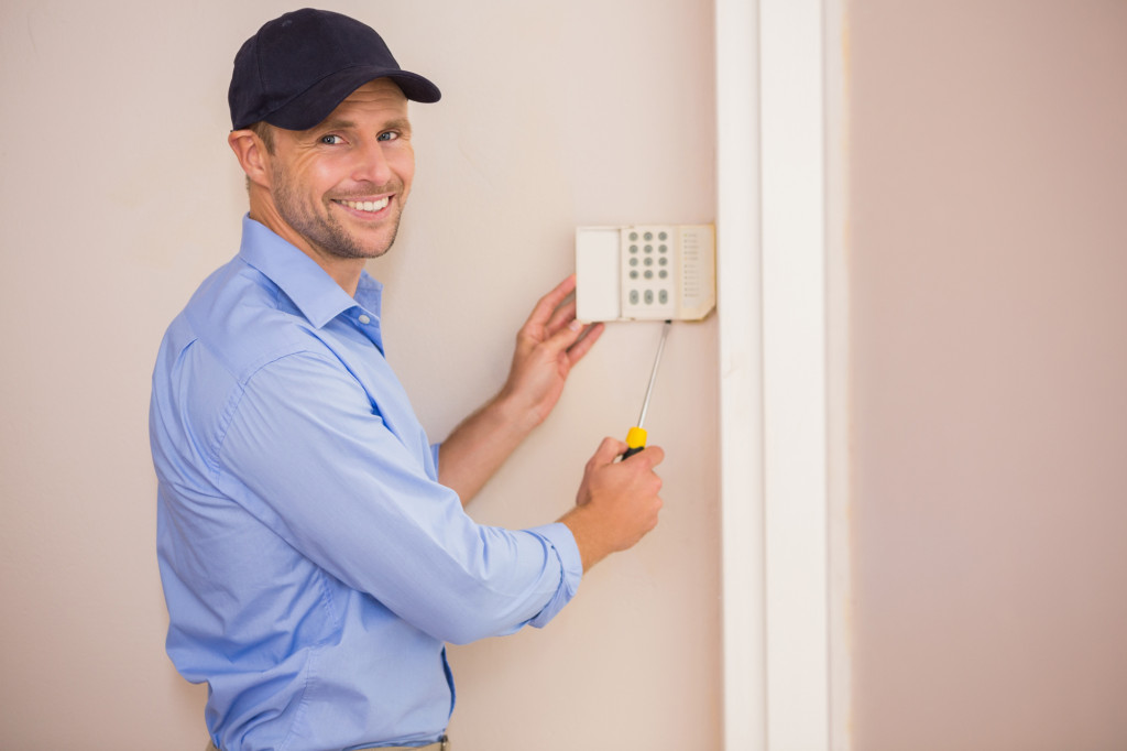 Smiling handyman fixing an alarm system
